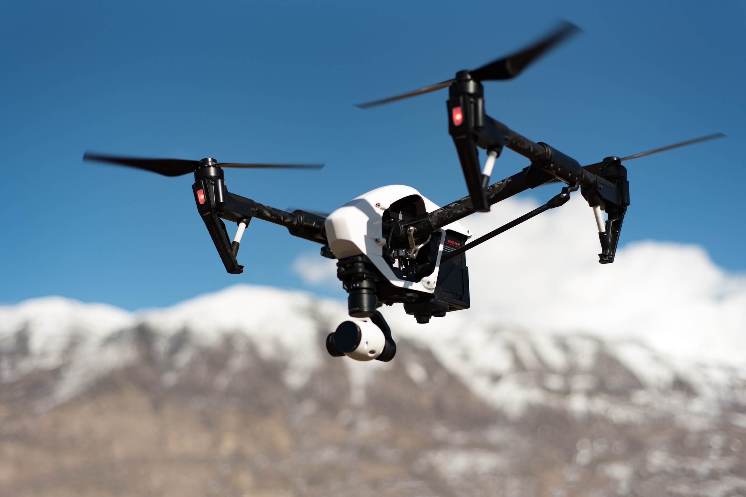 Carbon fiber drone flying near snowy mountains