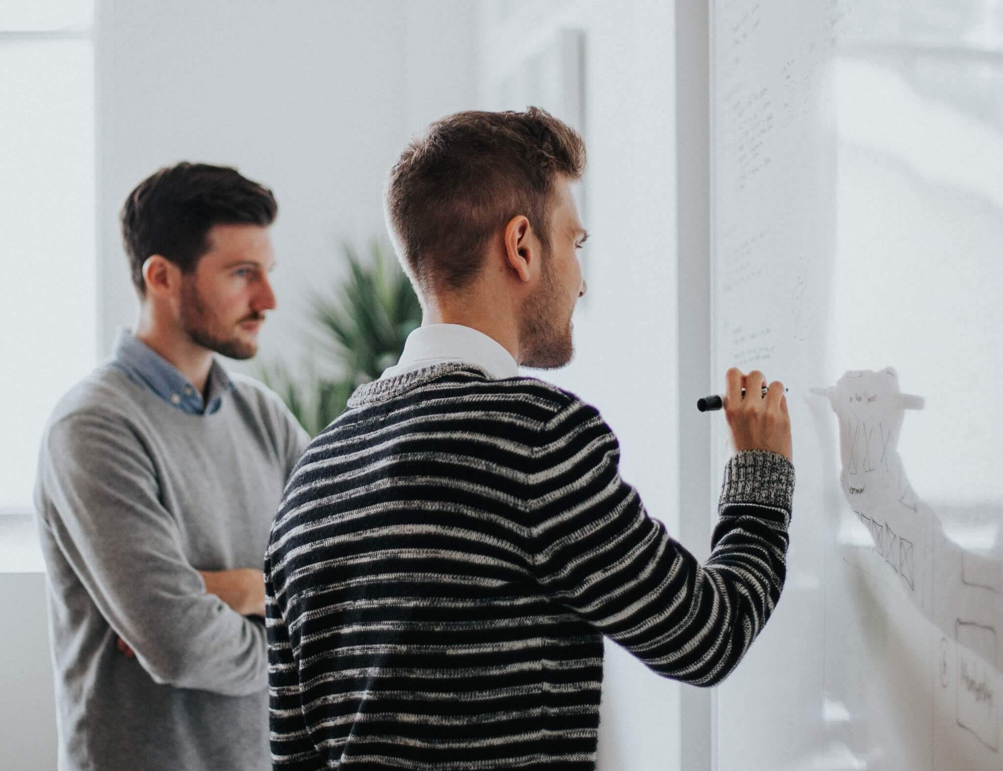 Two male engineers writing on a whiteboard
